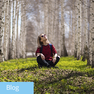 img des: Person sitting down, surrounded by trees, with a happy look on their face.