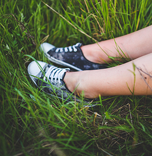 image of two feet wearing sneakers in the grass