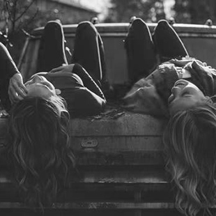 two girl laying on the hood of a car