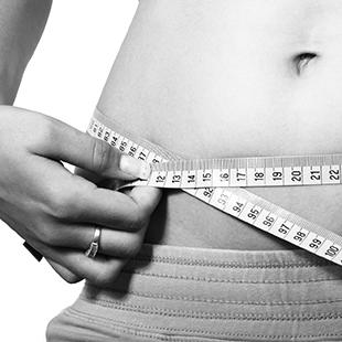 woman holding tape measure around waist