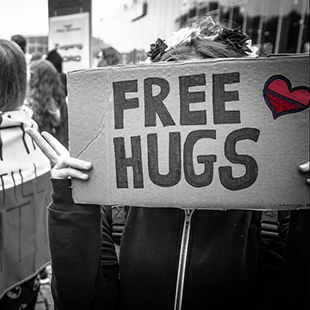 girl holding sign that says free hugs