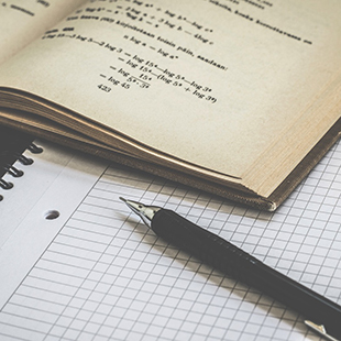 effective studying math book and pen over grid paper