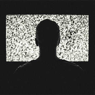man in front of tv showing static