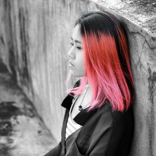 girl with pink hair leaned against a wall